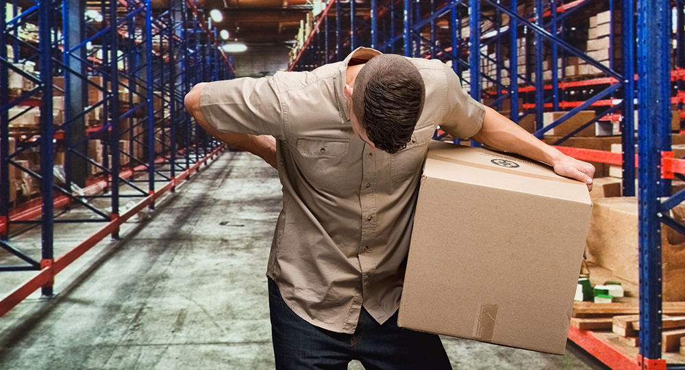 Worker with back pain holding cardboard box