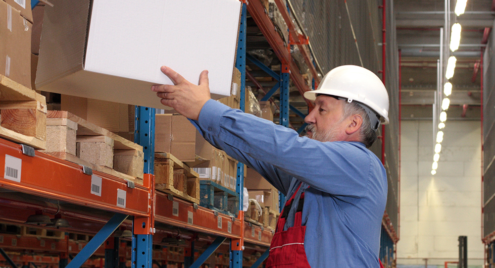 Warehouse employee placing a box on a shelf